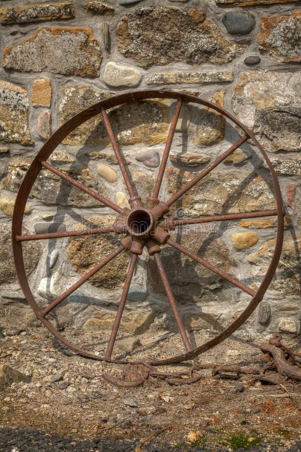 Rostigt vagnshjul som vilar mot en stenvägg inte 2 royaltyfri foto