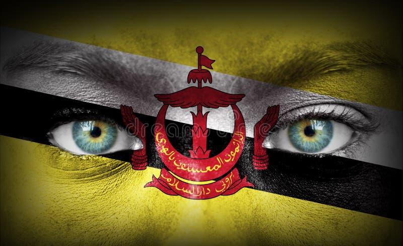 Rosto humano pintado com a bandeira de Brunei Darussalam foto de stock
