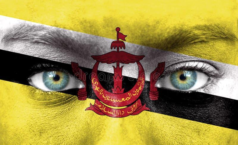 Rosto humano pintado com a bandeira de Brunei Darussalam imagens de stock royalty free
