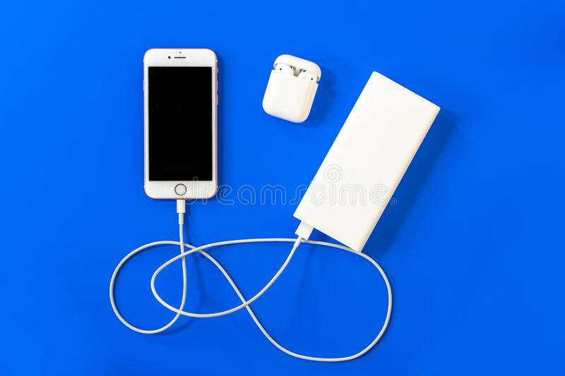 ROSTOV-ON-DON, RUSSIA - APRIL 28, 2018: Top view plastic white wireless Apple AirPods, charging, power bank, smartphone iphone 8,. Iphone 7, iphone 6, Lighning royalty free stock image
