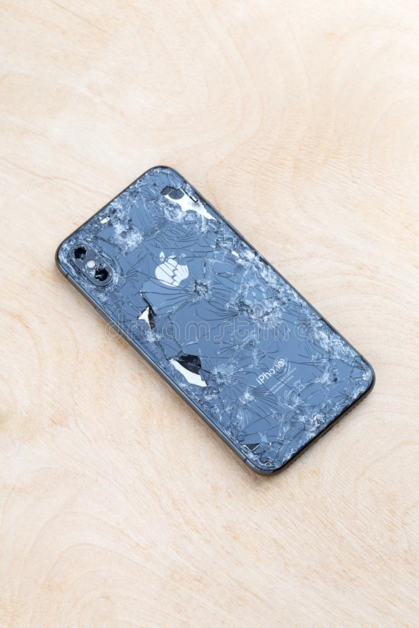 Broken iPhone XS lies on a wooden surface. Rostov-on-Don, Russia - December 2018. Broken iPhone XS lies on a wooden surface. New smartphone from the company stock photos
