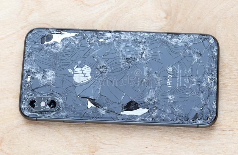 Broken iPhone XS lies on a wooden surface. Rostov-on-Don, Russia - December 2018. Broken iPhone XS lies on a wooden surface. New smartphone from the company royalty free stock photo