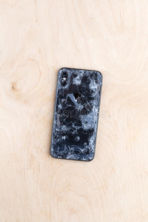 Broken iPhone XS lies on a wooden surface. Rostov-on-Don, Russia - December 2018. Broken iPhone XS lies on a wooden surface. New smartphone from the company royalty free stock image