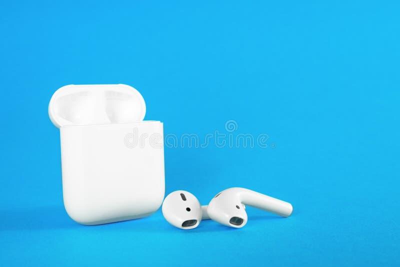 ROSTOV-ON-DON, RUSSIA - 24 febbraio 2019: Cuffie senza fili di Apple AirPods Bluetooth ed argomento di carico per il iPhone di Ap fotografie stock