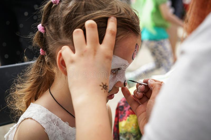 ROSTOV-ON-DON, RUSSIA - MAY, 2017: Animator drawing a cat makeup on the face of a girl. Children holiday, party concept royalty free stock photos