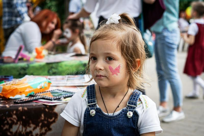 ROSTOV-ON-DON, RUSSIA - MAY, 2017: A girl with a painted butterfly on her face at a children`s party royalty free stock photo