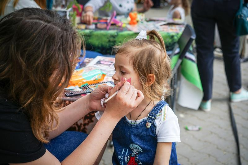 ROSTOV-ON-DON, RUSSIA - MAY, 2017: Woman painting face of kid outdoors. baby face painting. Children holiday, party concept stock photography