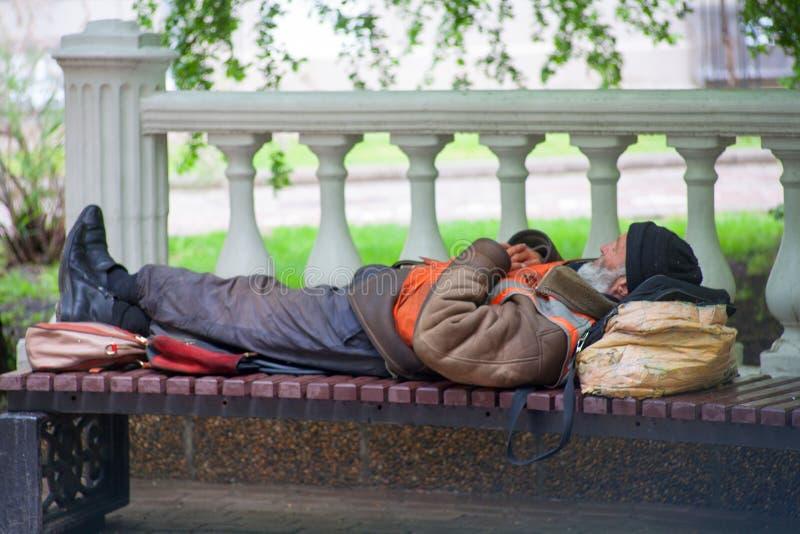 Rostov-na-Donu RYSSLAND - Maj 10,2017: En hemlös fattig man som en alkis sover på en bänk i en stad parkerar fotografering för bildbyråer