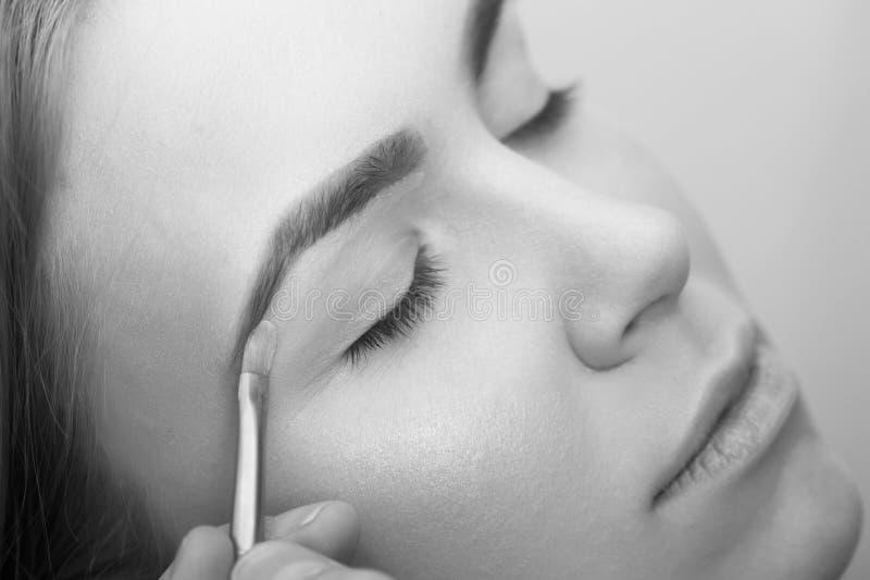 Rostro, cosméticos, skincare Salón de belleza Muchacha con los ojos cerrados que consiguen maquillaje en los párpados imágenes de archivo libres de regalías