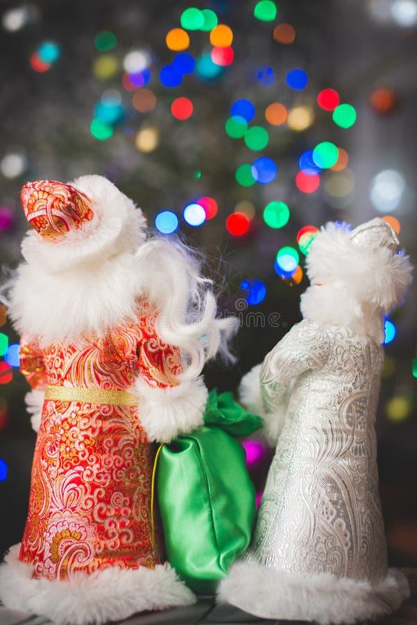 Rosyjscy Bożenarodzeniowi charaktery: Ded Moroz Santa i Snegurochka śnieżna dziewczyna wokoło choinki z prezent torbą, fotografia royalty free