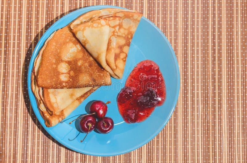 Rosyjscy tradycyjni naczynie bliny z wiśniami, dżemem i mlekiem, obraz stock