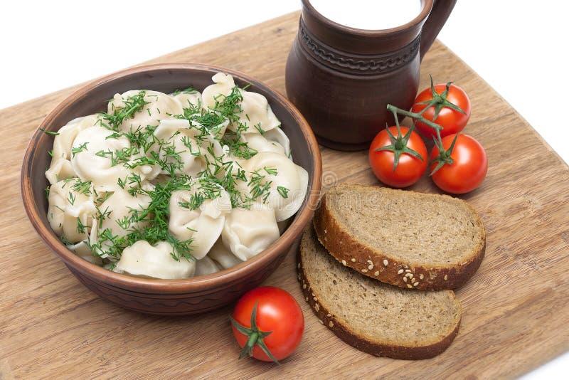 Rosyjska kuchnia: kluchy na talerzu, pomidorach i chlebie na, obraz royalty free