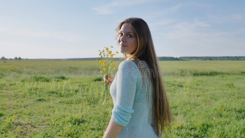 Rosyjska młoda dziewczyna z bukietem kwiaty w rękach pozuje na ciepłym lato wieczór w polu zdjęcia stock