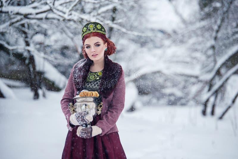 Rosyjski ludu stylu rudzielec dziewczyny mienia samowar w futerkowym żakiecie w śnieżnej zimie fotografia royalty free