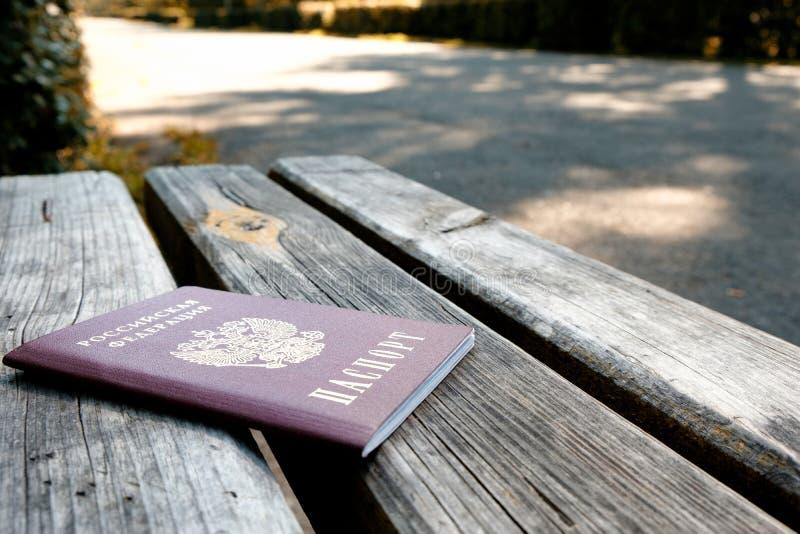 Rosyjski paszport na drewnianej ławce na letnim dniu tło brukująca ścieżka fotografia royalty free