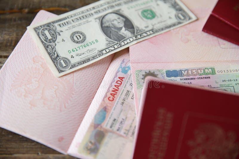 Rosyjski paszport z Schengen i kanadyjczykiem wizował i pieniądze - jeden dolar Wiza znaczka podróży paszport Wakacje i podr?? zdjęcie royalty free