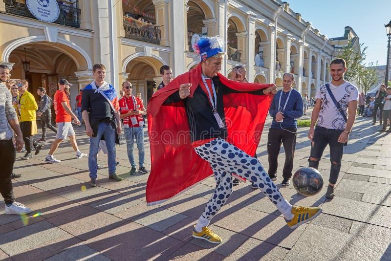 Rosyjski piłki nożnej fan z szalenie kapeluszem kopie piłkę, St Petersburg zdjęcie stock