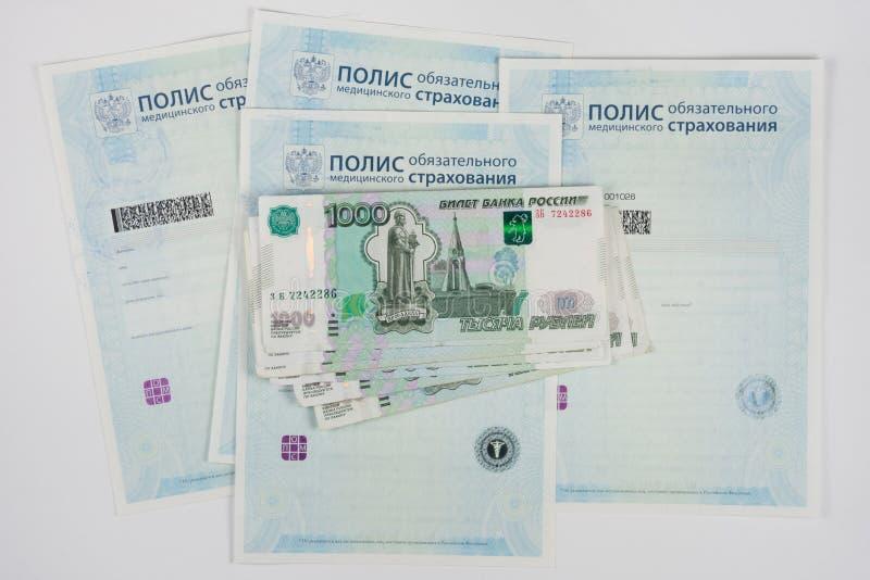 Rosyjski pieniądze jest na polisie obowiązkowy ubezpieczenie medyczne, biały tło obraz stock