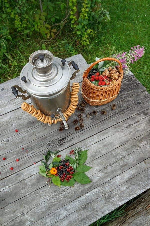 Download Rosyjski Samowar Na Nieociosanym Drewnianym Stole Z Jagodami I Kwiatami Obraz Stock - Obraz złożonej z stary, emocje: 57657403