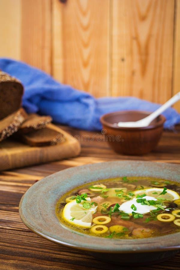 Rosyjski zupny Solyanka z kwaśną śmietanką na drewnianym tle fotografia stock