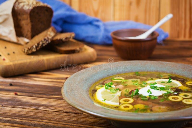 Rosyjski zupny Solyanka z kwaśną śmietanką na drewnianym tle zdjęcie royalty free