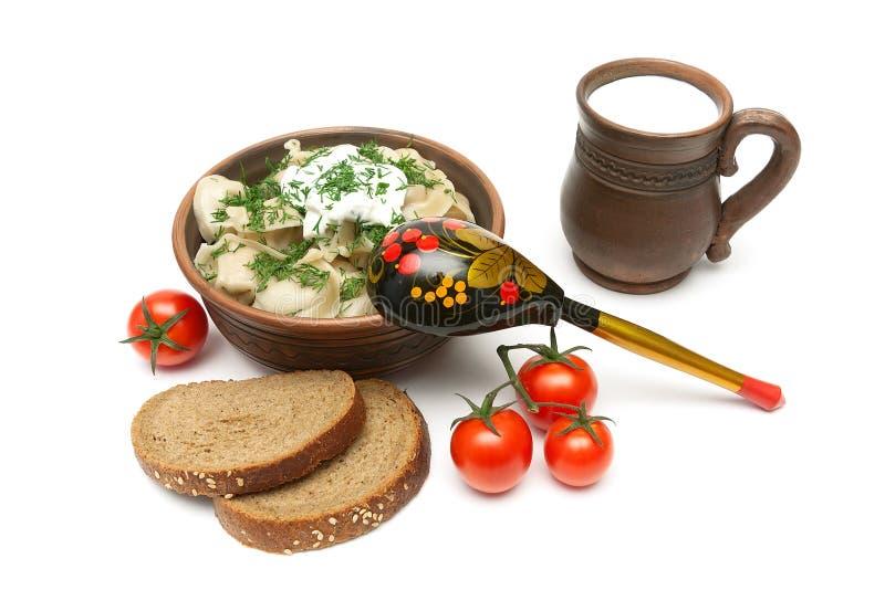 Rosyjskie kluchy w pucharze, chlebie, mleku i pomidorach na a glinianych, obrazy stock