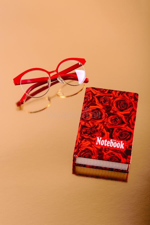Rot-eingefaßte Gläser und ein rotes Notizbuch auf einem goldenen Hintergrund stockfotografie