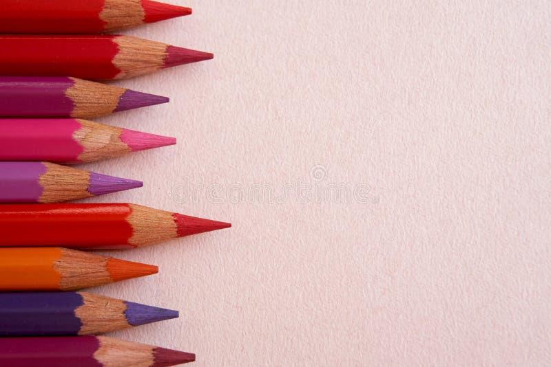 Rot farbige Bleistifte über einem rosa Hintergrund stockbild