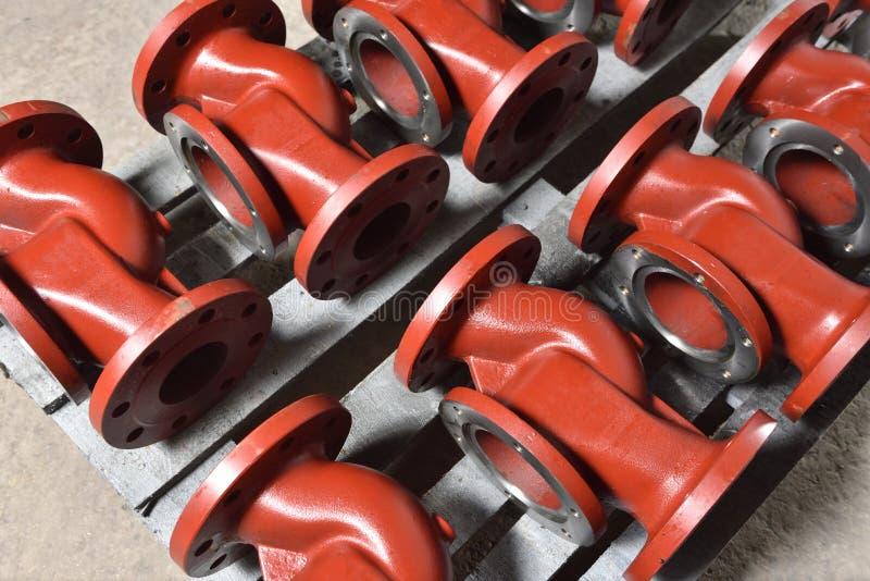 Rot gefärbte Metallrohre, Armaturenbretter, die nach dem Malen für die Montage auf einem Holzbrett liegen Der Hauptteil lizenzfreies stockfoto