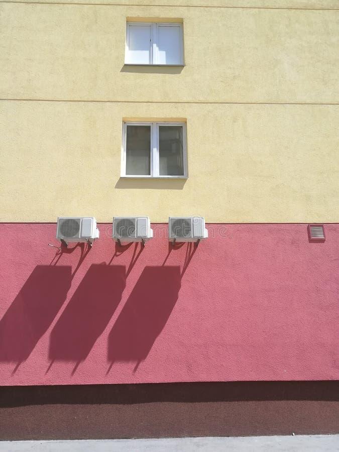 Rot-gelbes Gebäude mit drei Klimaanlagen stockbilder