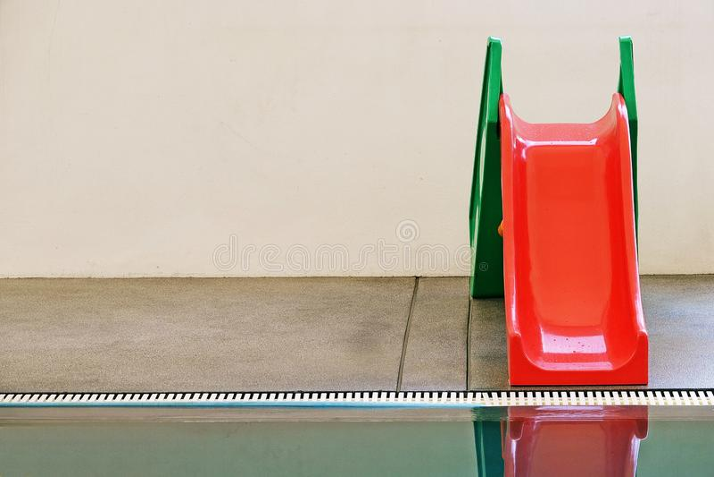 Rot, grün, Wasserschieber im Swimmingpool stockfotografie