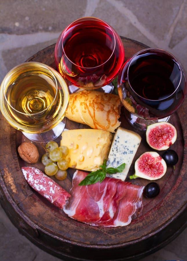 Rot, rosafarbene und weiße Gläser und Flaschen Wein Käse, Feige, Traube, Prosciutto und Brot auf altem hölzernem Fass Ansicht von lizenzfreie stockbilder