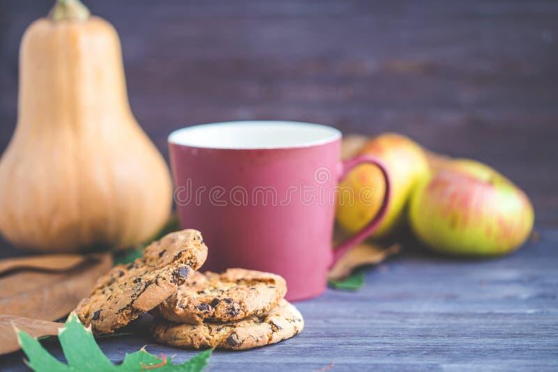 Rot und Orange färbt Efeublattnahaufnahme Plätzchen, Kürbis lässt Kaffee-Äpfel auf einem hölzernen Hintergrund stockfoto