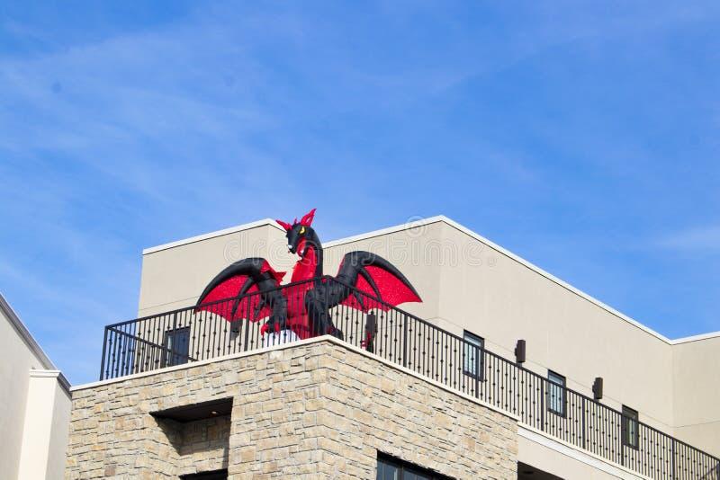 Rot und Schwarzes explodieren Drachen auf Balkon des Geschäftsgebäudes gegen blauen Himmel für Halloween lizenzfreie stockfotografie