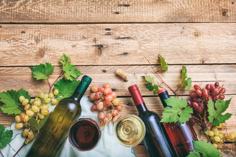 Rot und Weißweingläser und -flaschen auf hölzernem Hintergrund, Kopienraum Frische Trauben und Traubenblätter als Dekoration stockfotografie