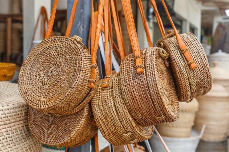 Rota hecha a mano del Balinese tejida alrededor de los bolsos con las manijas de cuero en una tienda de la calle Bali, Indonesia fotos de archivo