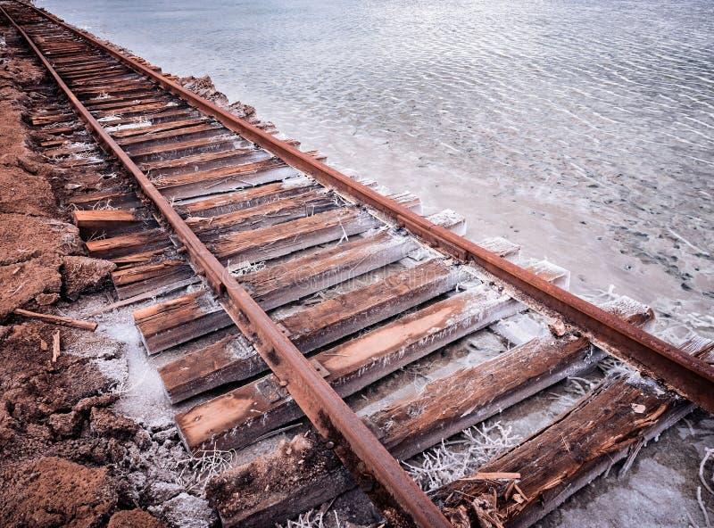 Rotaie razy arrugginite e traversine marcie coperte di sale sui vecchi binari ferroviari su un monticello nel lago di estrazione  fotografie stock