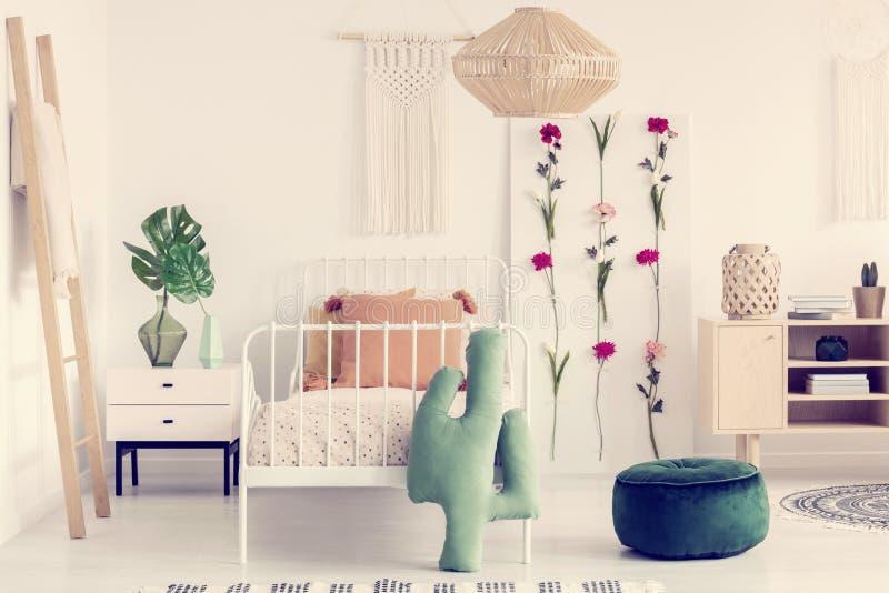 Rotankroonluchter boven enig metaalbed met gekletterd dekbed in het binnenland van de bohoslaapkamer met natuurlijke meubilair en royalty-vrije stock afbeelding