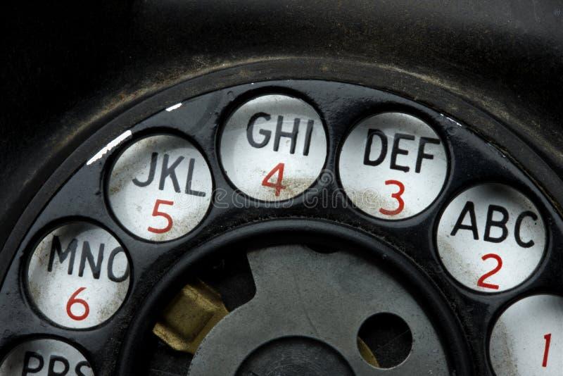 Rotary dial on old telephone. Macro shot rotary dial on grungy, old telephone stock photography