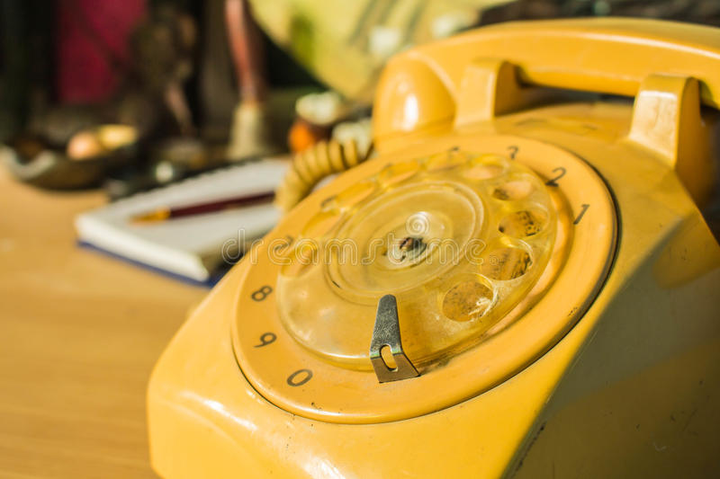 The rotary dial phone. On a wooden table stock photo