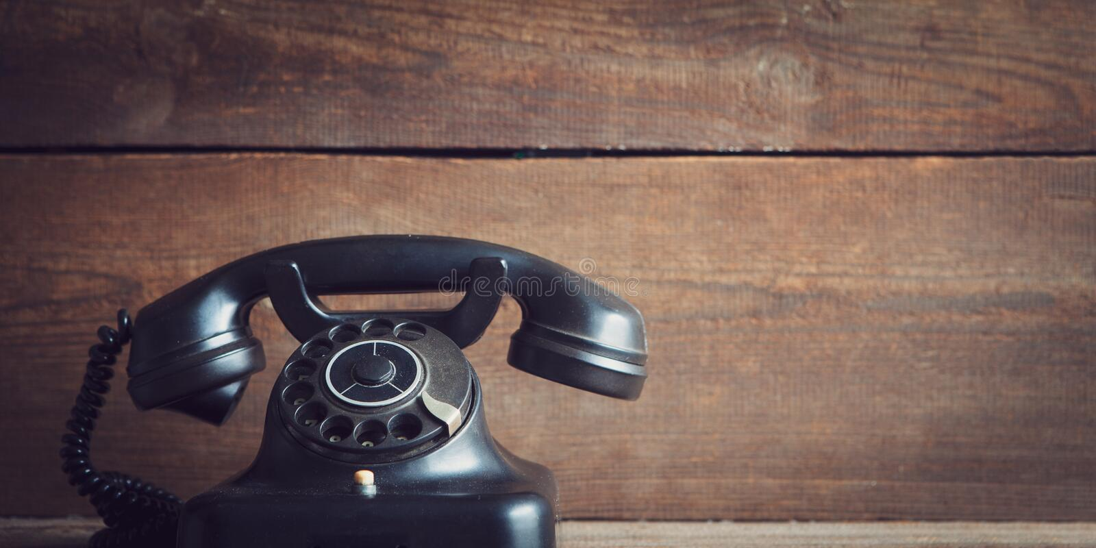 Rotary dial telephone. Vintage rotary dial telephone on wooden board with copy space stock images