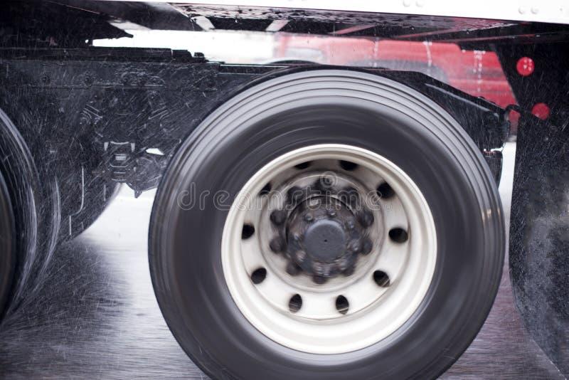 Wheels of big rig semi truck raises rain dust from the wet road. Rotary wheels of long haul moving on the highway big rig semi truck with semi trailer raises royalty free stock photos