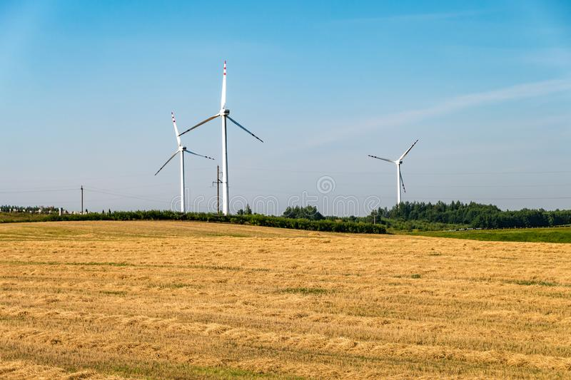 Rotating blades of a windmill propeller. Wind power generation. Pure green energy. Rotating blades of a windmill propeller on blue sky background. Wind power stock photos