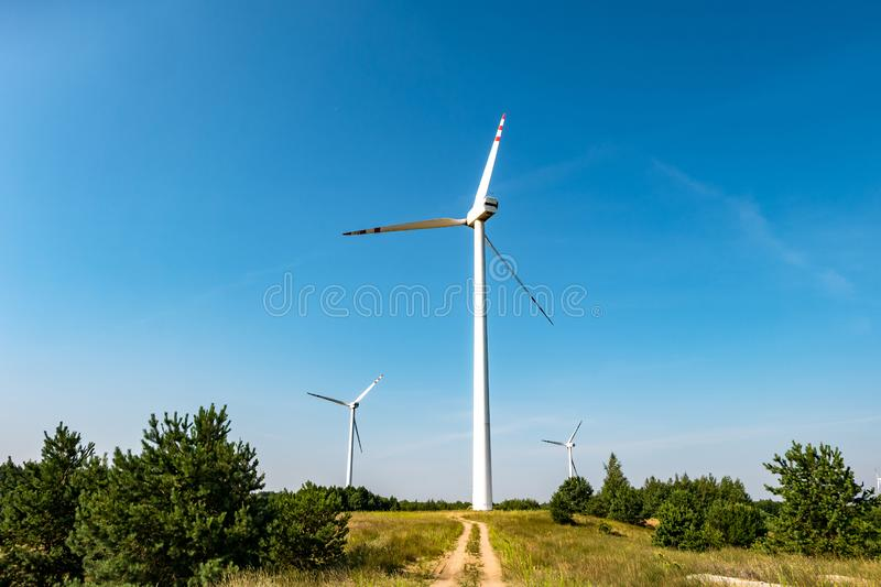 Rotating blades of a windmill propeller. Wind power generation. Pure green energy. Rotating blades of a windmill propeller on blue sky background. Wind power royalty free stock photography