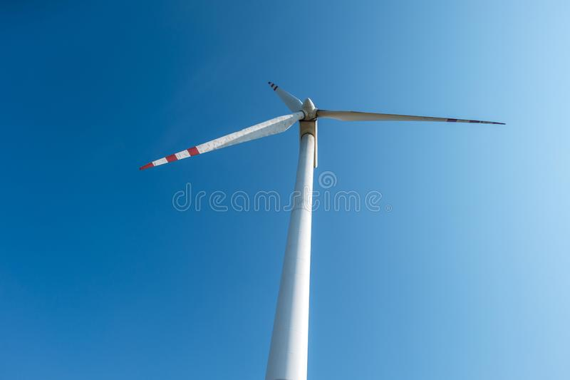 Rotating blades of a windmill propeller. Wind power generation. Pure green energy. Rotating blades of a windmill propeller on blue sky background. Wind power royalty free stock images