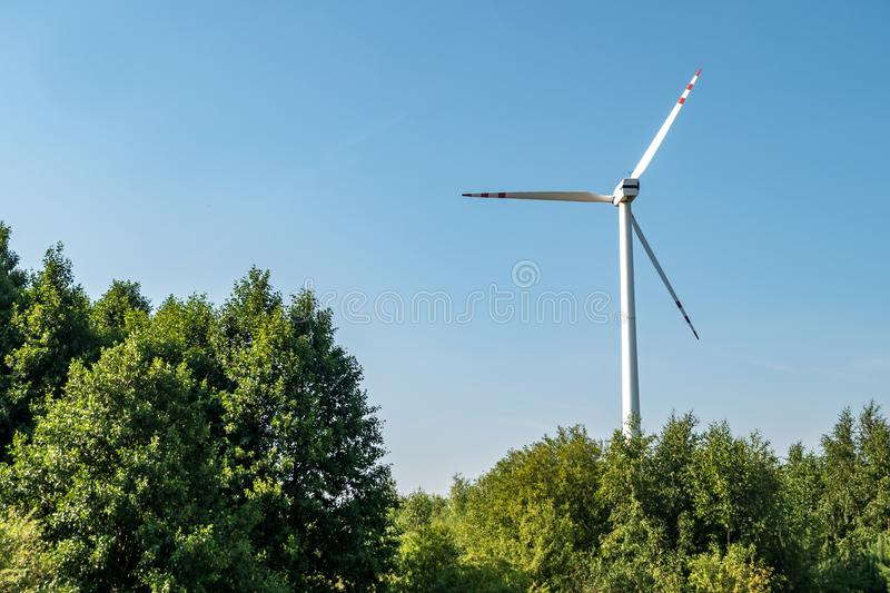 Rotating blades of a windmill propeller. Wind power generation. Pure green energy. Rotating blades of a windmill propeller on blue sky background. Wind power stock photo