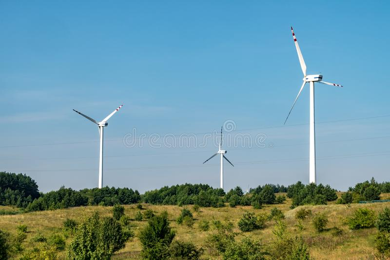 Rotating blades of a windmill propeller. Wind power generation. Pure green energy. Rotating blades of a windmill propeller on blue sky background. Wind power royalty free stock photo