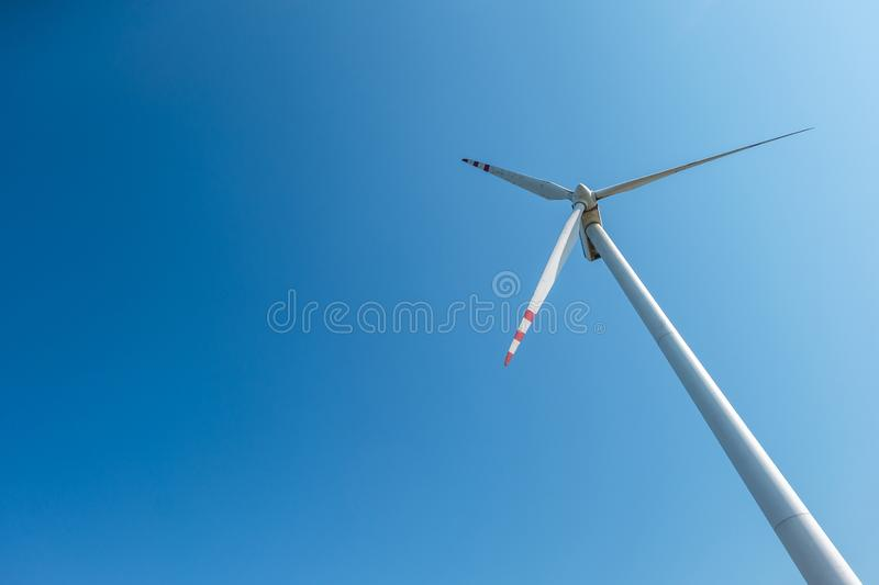 Rotating blades of a windmill propeller on blue sky background. Wind power generation. Pure green energy.  stock photography