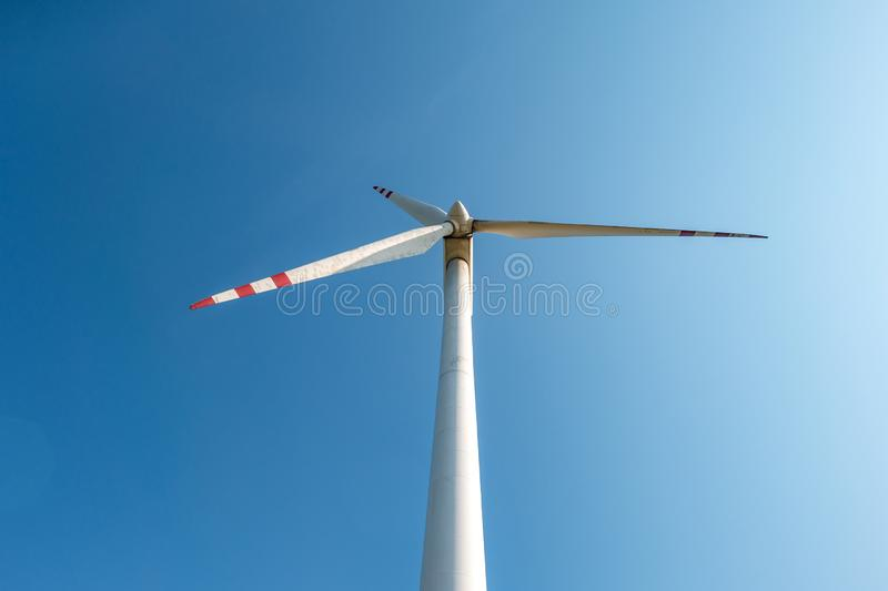 Rotating blades of a windmill propeller on blue sky background. Wind power generation. Pure green energy.  royalty free stock photos