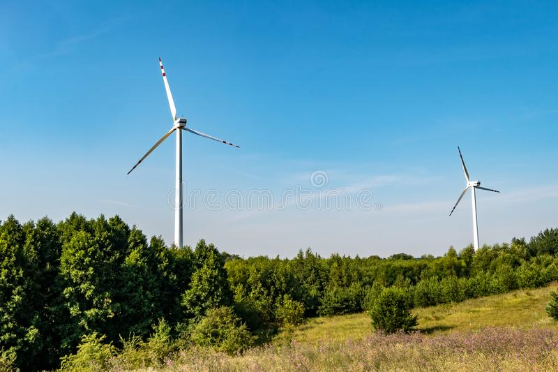 Rotating blades of a windmill propeller on blue sky background. Wind power generation. Pure green energy.  royalty free stock photo